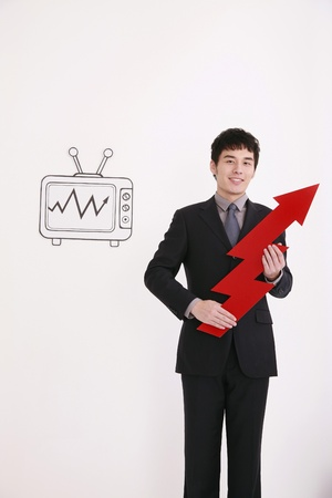 Businessman holding arrow sign, television on the wall