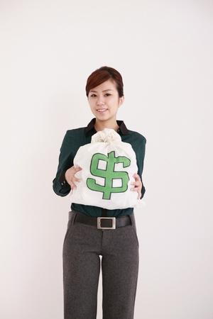 Businesswoman holding up money bag Stock Photo - 9287943