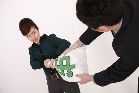 tugging: Business people pulling at money bag