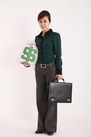 Businesswoman holding briefcase and money bag photo