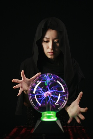 crystal gazing: Woman with cape using crystal ball Stock Photo