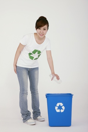 Woman throwing plastic bottle into recycling bin Stock Photo - 9288780