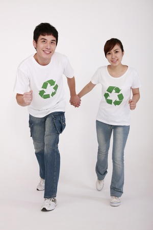 Woman and man wearing t-shirts with recycling symbol holding hands photo