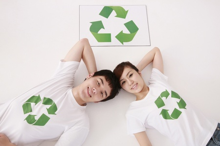 Man and woman wearing t-shirts with recycling symbol lying on the ground Stock Photo - 9288490
