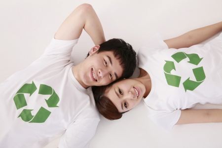 Man and woman wearing t-shirts with recycling symbol lying on the ground Stock Photo - 9288016