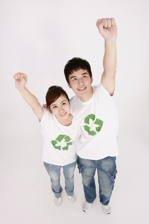 cheer full: Man and woman wearing t-shirts with recycling symbol raising arms Stock Photo