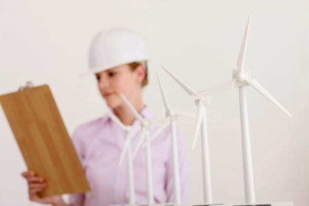 A row of wind turbine models, businesswoman with hardhat looking at clipboard in the background photo