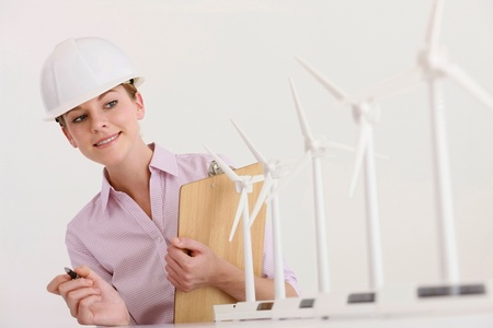 Businesswoman with hardhat holding pen and clipboard while looking at wind turbine models photo