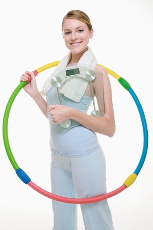 Woman holding plastic hoop and weight scale photo