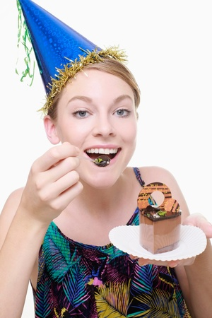 Woman with party hat eating birthday cake photo