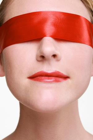 Woman being blindfolded with red ribbon photo