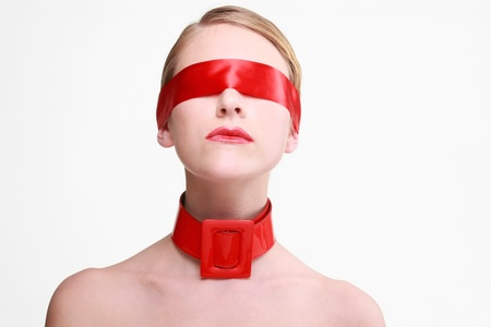 Woman with red ribbon covering her eyes and red belt on her neck photo