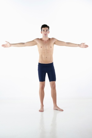 Shirtless man in tights with his arms outstretched photo