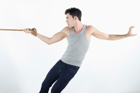 Man with hand tied to a rope, pulling hard photo
