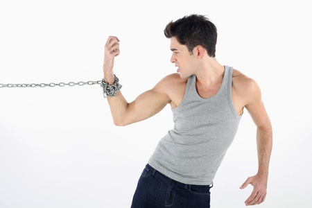 tied up: Man with hand tied to a chain, pulling hard