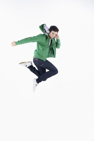 Man jumping in the air while listening to music on MP3 player photo