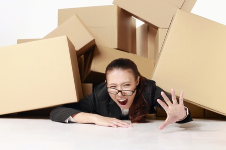 lying forward: Businesswoman crying for help while being buried under a pile of boxes  Stock Photo