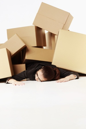 fainted: Businesswoman lying unconsciously on the floor after being buried under a pile of boxes