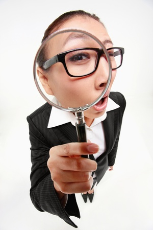 magnifying glass: Businesswoman looking through a magnifying glass