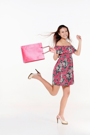 Woman skipping happily after shopping Stock Photo - 9288864