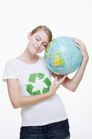 Woman with recycling symbol on her T-shirt resting her head on a globe photo