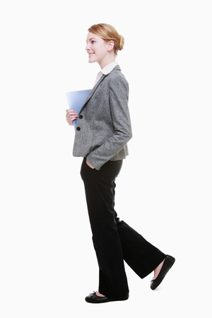 Businesswoman holding a file while walking Imagens