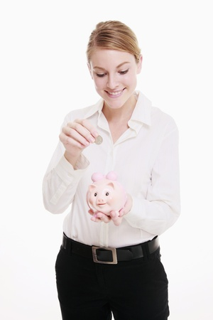 Businesswoman putting coin into piggy bank photo