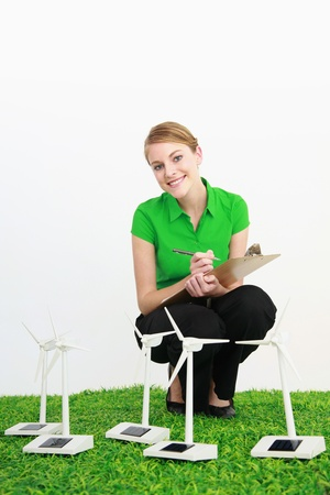 Businesswoman writing on clipboard while looking at wind turbine models photo