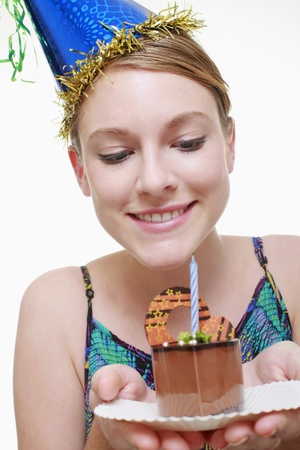 Woman with party hat holding a slice of birthday cake Stock Photo - 9521219