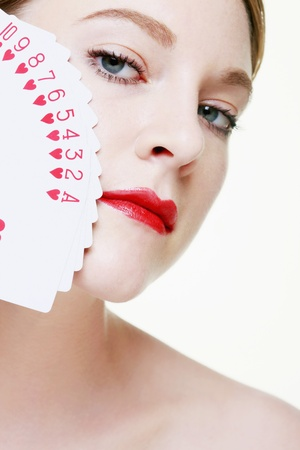 Woman with fanned out playing cards on her face photo