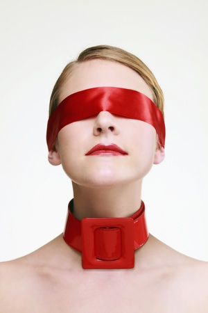 Woman with red ribbon covering her eyes and red belt on her neck Stock Photo - 9521400