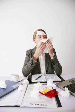Businesswoman blowing her nose with tissue photo