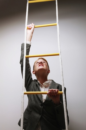 Businesswoman climbing rope ladder photo
