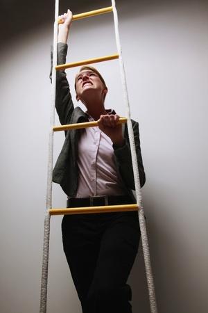 rope ladder: Businesswoman climbing rope ladder