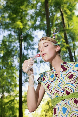 Woman blowing soap bubbles photo
