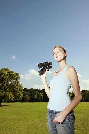 Woman holding binoculars and looking away photo