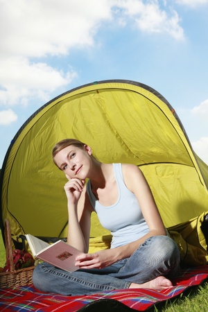 Woman reading book while camping in the park photo