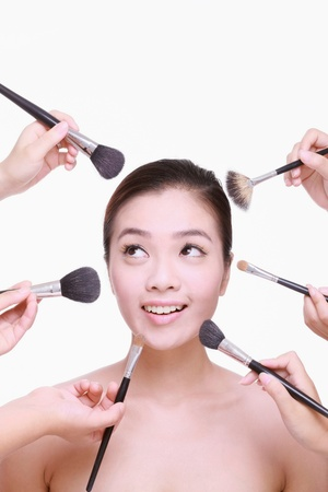 Hands applying make-up on woman's face Stock Photo - 9521199
