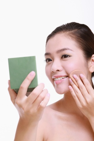 Woman holding a compact mirror and applying foundation on her face photo