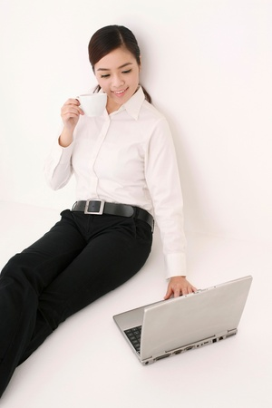 Businesswoman drinking coffee while using laptop photo