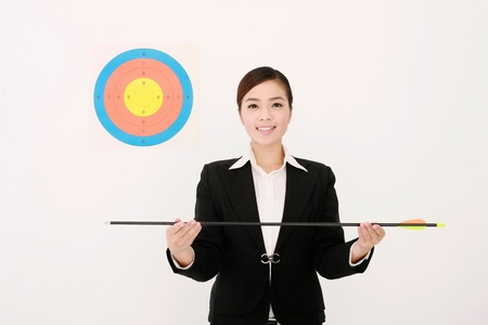 Businesswoman with target next to her head, holding an arrow Stock Photo - 9521008