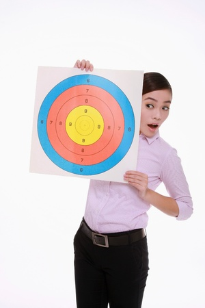 Businesswoman holding target and looking at it Stock Photo - 9521515