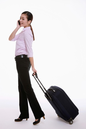 Businesswoman talking on the mobile phone while pulling her luggage photo