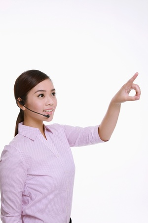 Businesswoman talking on telephone headset and pointing Stock Photo - 9521249