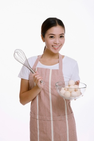 Woman holding whisk and a bowl of eggs photo
