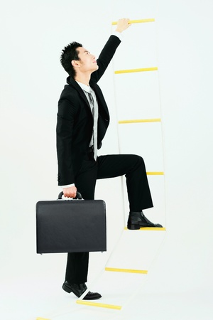 Businessman climbing up rope ladder Stock Photo - 9520787
