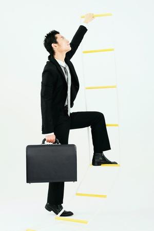 Businessman climbing up rope ladder Stock Photo - 9520787