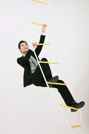 rope ladder: Businessman climbing up rope ladder Stock Photo