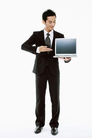 Businessman showing a laptop Stock Photo - 9520560