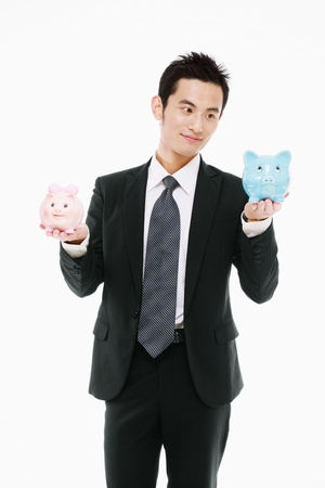 Businessman holding a pink and a blue piggy bank photo